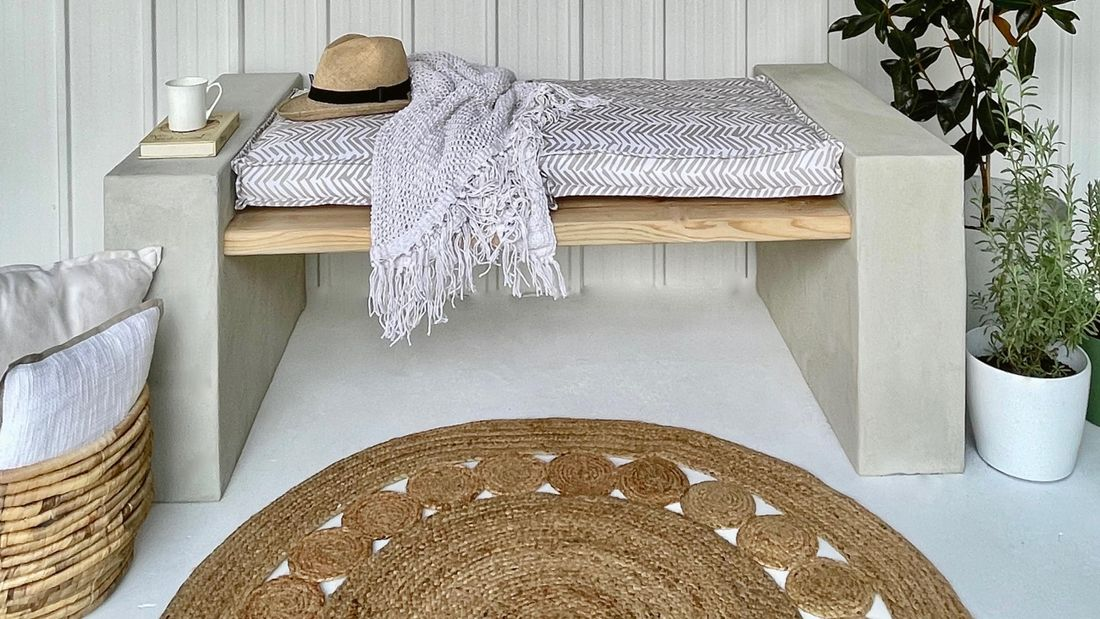 Block bench with timber slats, hat, rug and plant