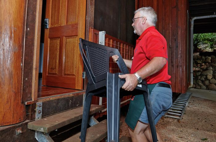 A Bunnings team member bringing a black outdoor chair inside the home