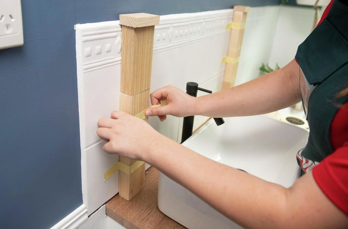 A person taping blocks of wood to a tiled wall above a basin in a bathroom
