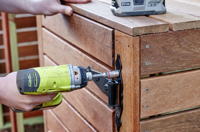 Person attaching a hinge to a timber door.