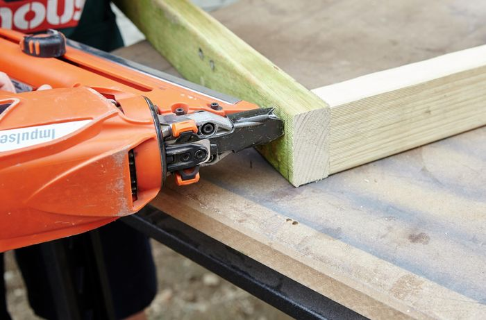 Framing gun putting two timbers together.