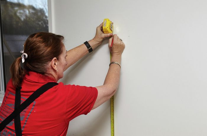 A woman marking a plasterboard wall using a measuring tape and pencil