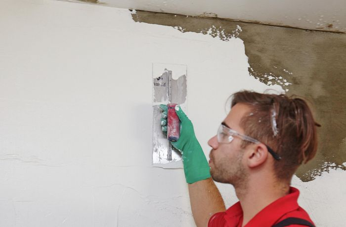 Plaster being applied to an indoor wall by a Bunnings team member with a trowel