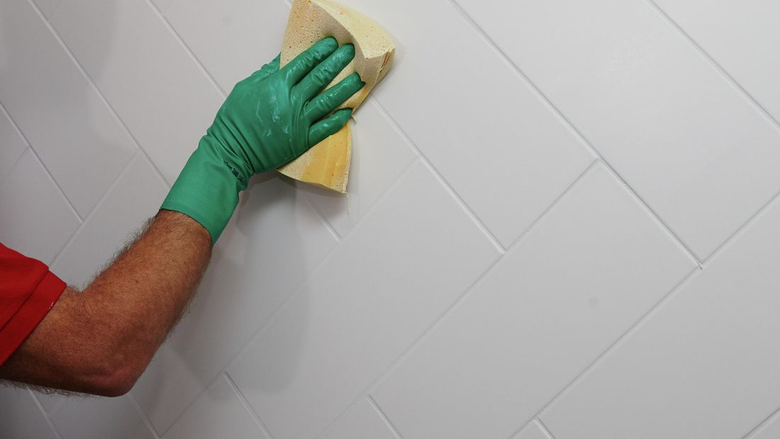 A sponge being used to spread grout into gaps between tiles on a wet wall
