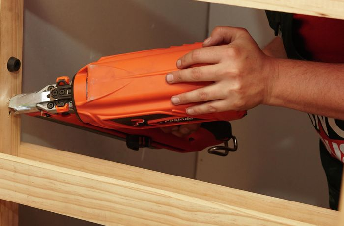 A person using a nail gun to fix a door frame to a wall stud