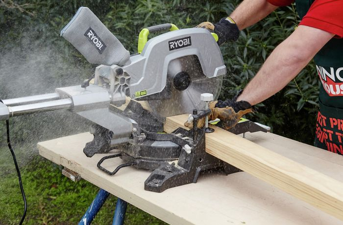 A mitre saw being used to cut lengths of timber to size