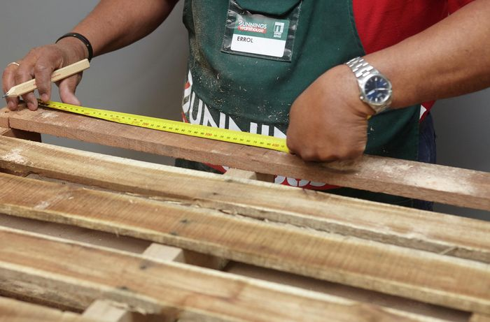 Person measuring and marking timber slats with tape measure and pencil