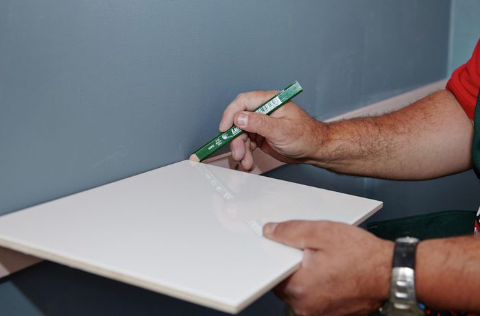 Person holding tile against wall and marking the wall with pencil.