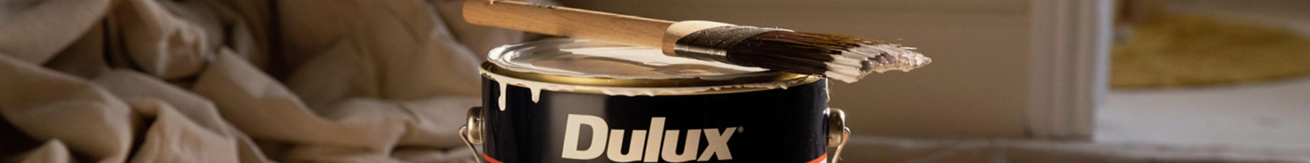 Dulux wash & wear paint with a used paint brush covered in white paint residue sitting atop of the can