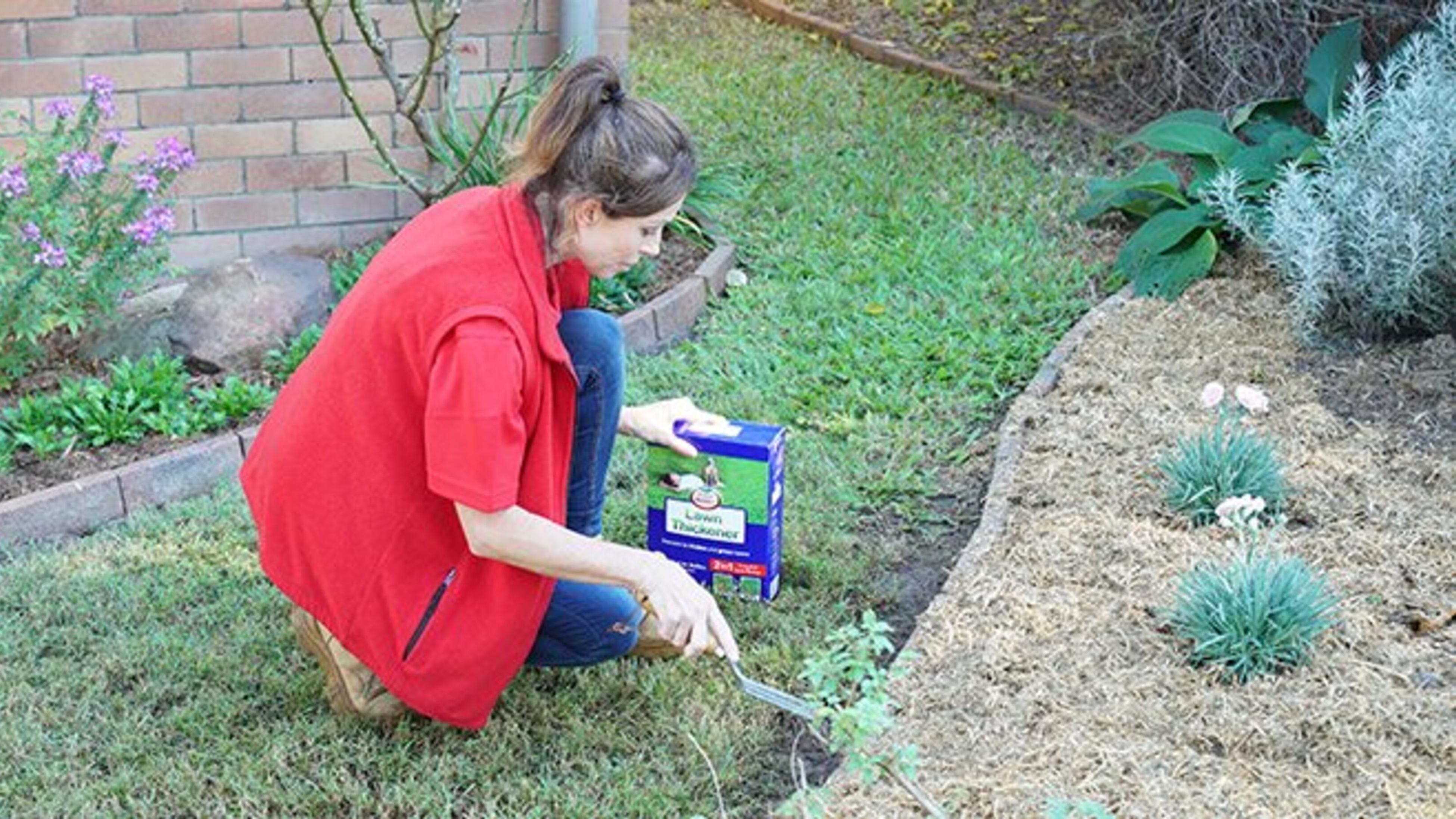 A Bunnings team member laying lawn thickener