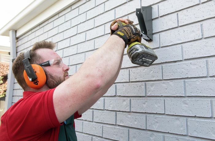 Person drilling bracket onto wall using bolts and drill