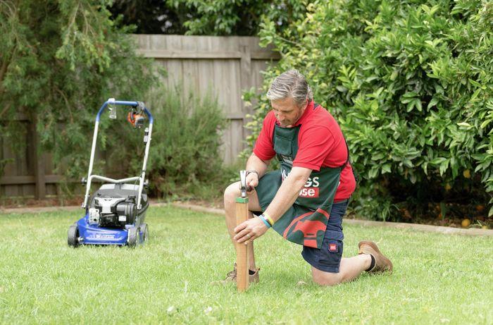 Bunnings team member kneeling down using a hammer on a garden stake