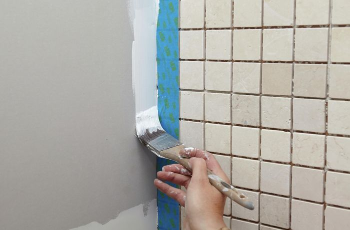 A person painting down the edge of a plasterboard wall next to a tiled wall with masking tape