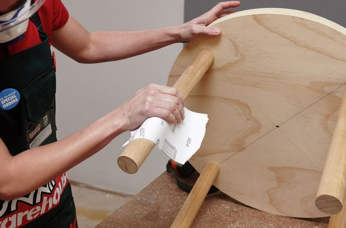A person sanding a dowel leg on a round table