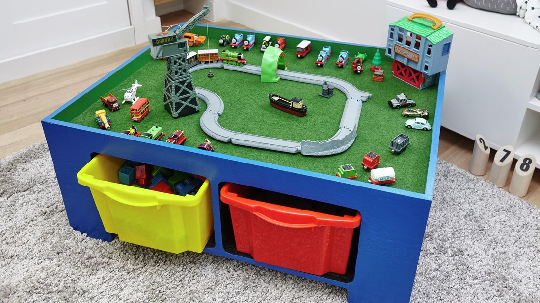 A blue table with a mini train set and toys on top and two storage tubs underneath