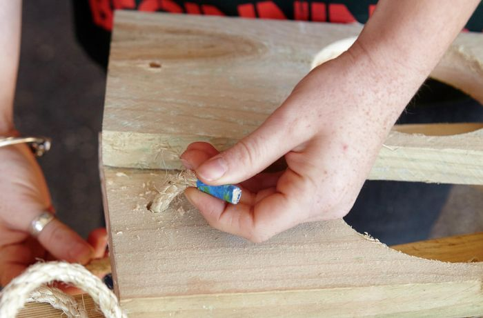 A person threading rope through a hole in a pine board