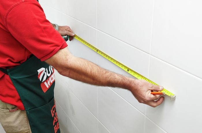 A person measuring a white tiled wall