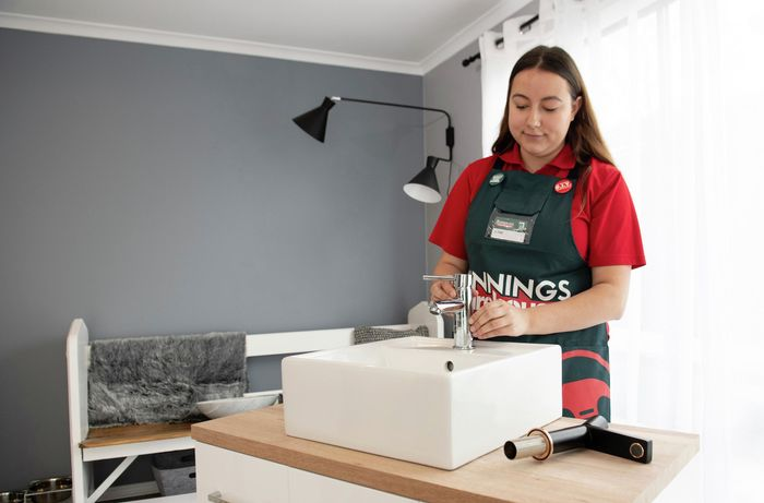 Bunnings team member adjusting the fit of the tap on the sink