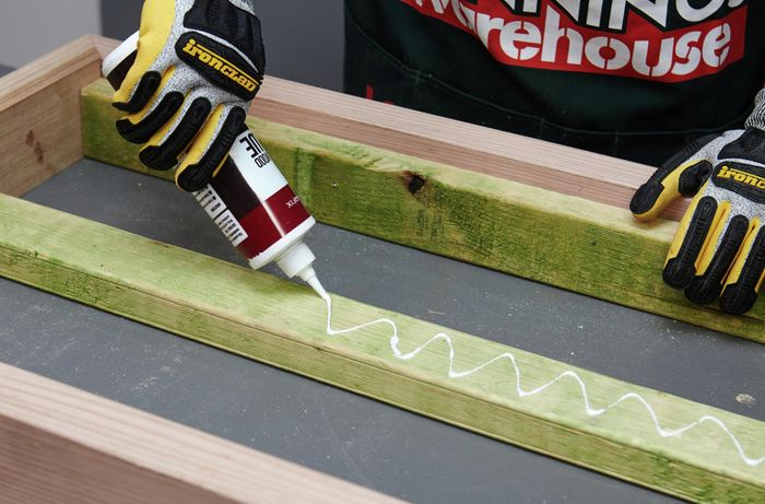 Glue being applied to a length of wood in a zig zag pattern