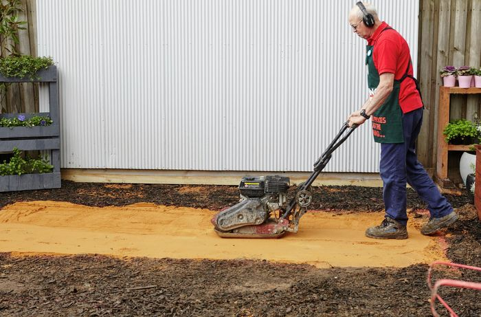Man wearing ear muffs compacting sand using a compactor