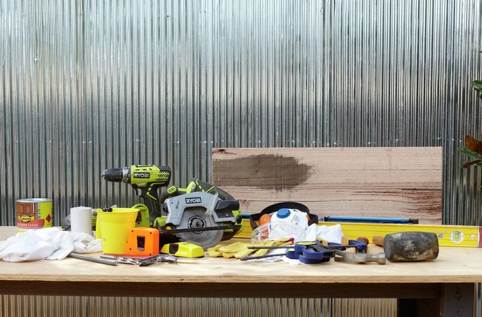Various tools and materials needed to prepare and install timber wall shelves.