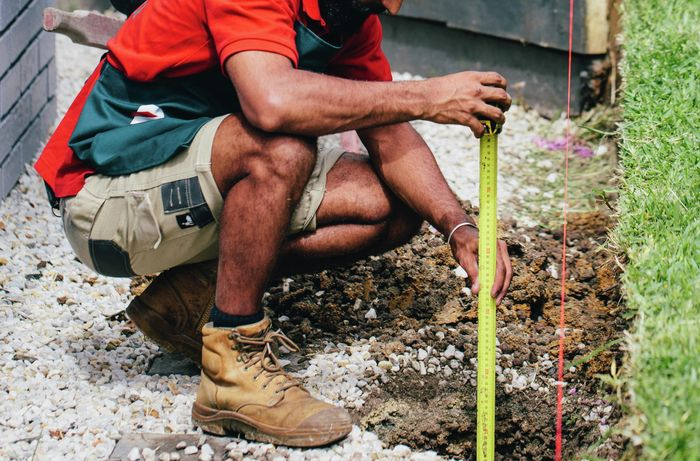 Tape measure and string being used to mark out the position of a retaining wall