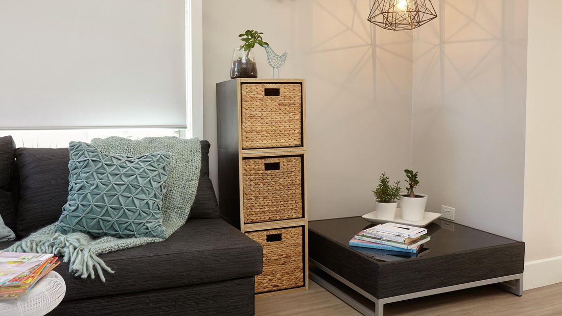 A wooden storage box with three wicker baskets in a warmly lit lounge room setting next to a modern black coffee table