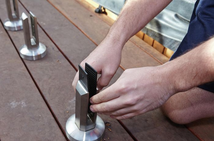 Person inserting metal plates and grips into mini post.