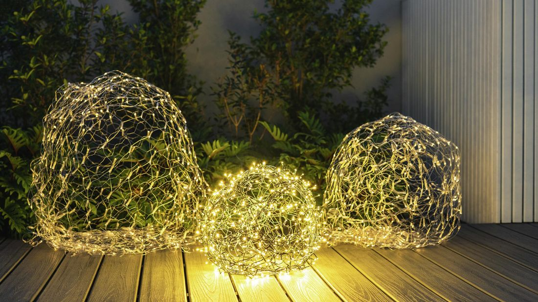 Three chicken wire baubles illuminated by fairylights sitting on an outdoor deck