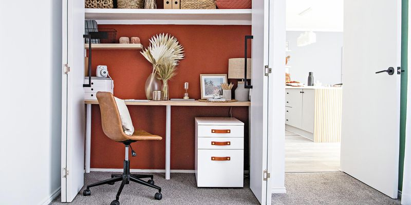 Office space with a desk inside a closet, leather office chair and white set of drawers.