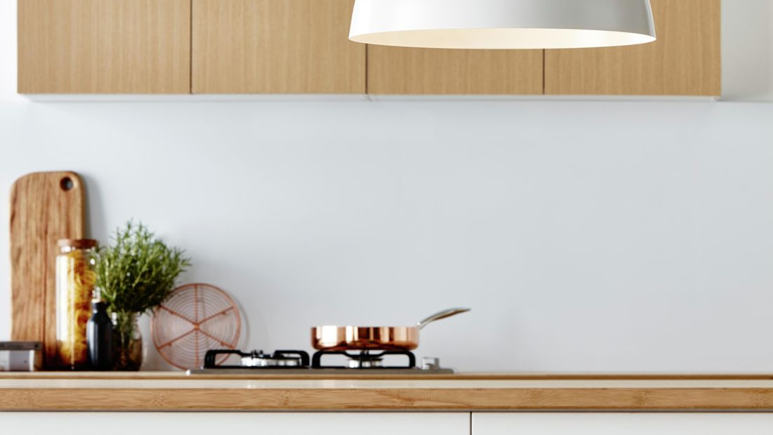 White light with an energy-efficient light bulb against a light wood panel.