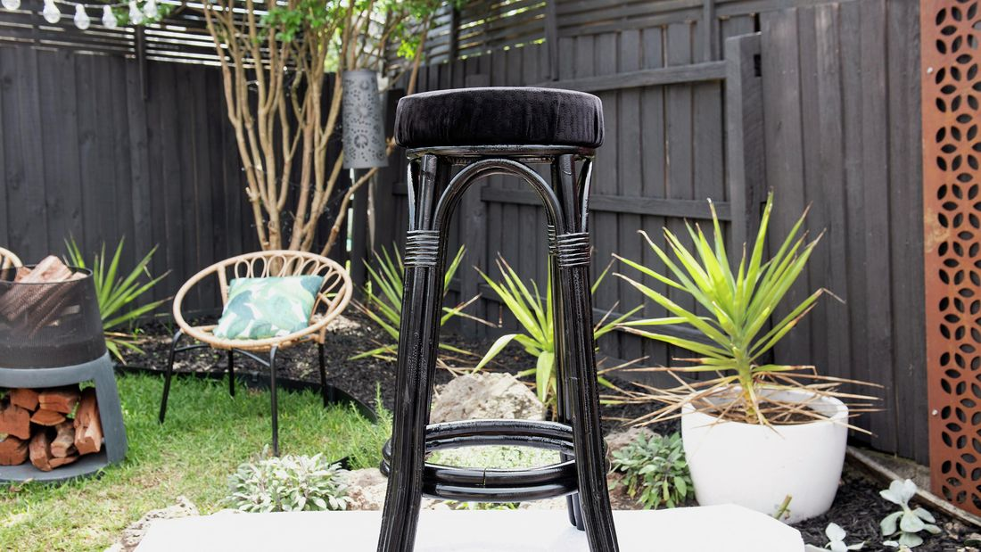 Cane bar stool painted black with black fabric seat