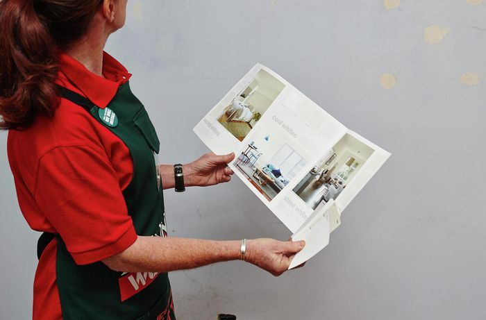 Bunnings team member looking at the wall and painting options