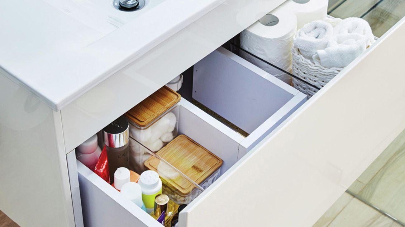 Opened vanity drawer organised by dividers housing bathroom lotions, toilet paper and towel.