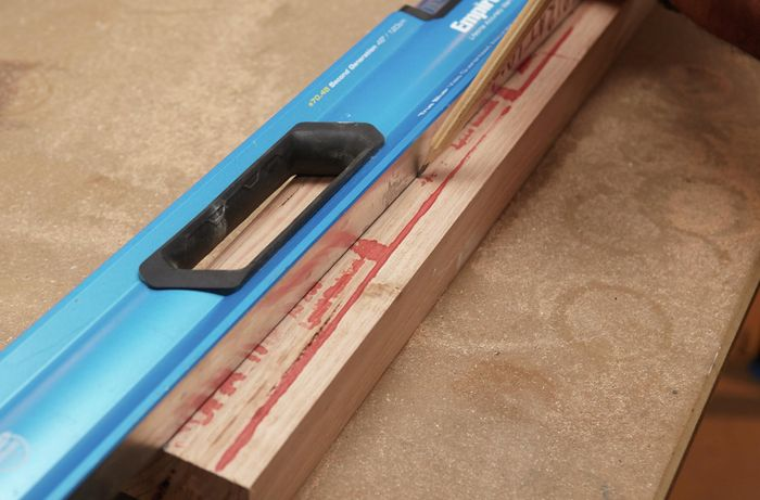 Person marking timber using pencil and spirit level