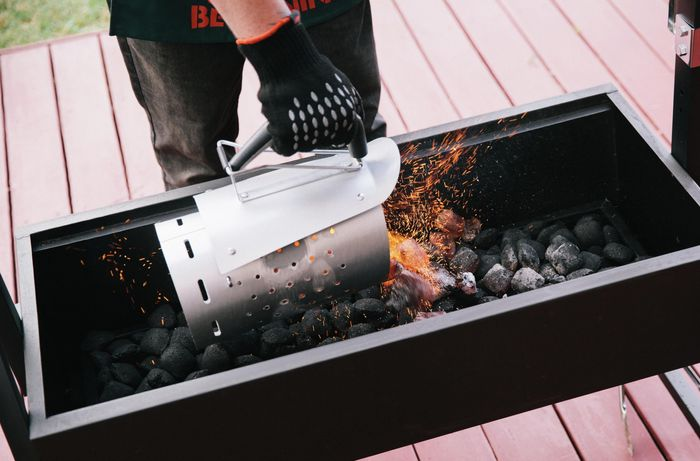 Person pouring hot charcoal briquettes into a smoker