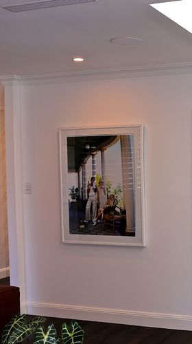 Framed family picture hung on wall underneath an LED downlight