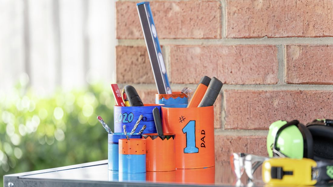Collection of tools sitting in six painted tins which are decorated with phrases like '#1 dad'