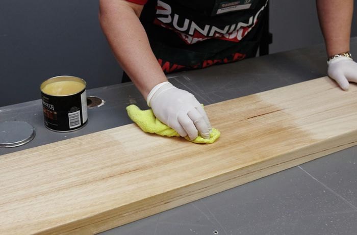Person wearing gloves using a cloth to varnish a timber book shelf.