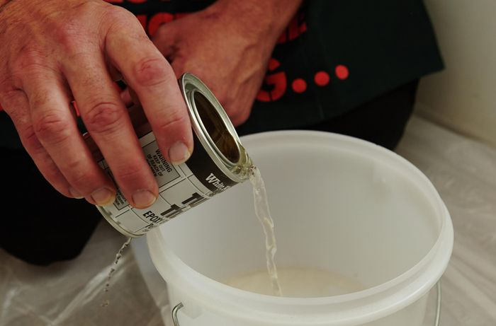 A person pouring clear liquid from a tin into a plastic container