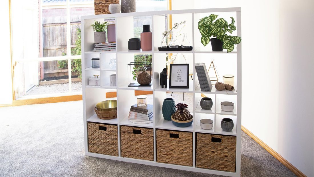 Cube unit with woven boxes, plants and other decorative items.