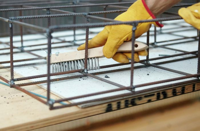 A wire brush being used to clear away slag from a weld in a wire mesh frame