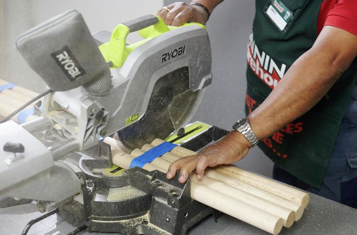 A mitre saw being used to cut several bar stool legs at once