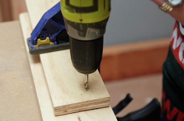A person drilling through a piece of plywood clamped to another piece of wood