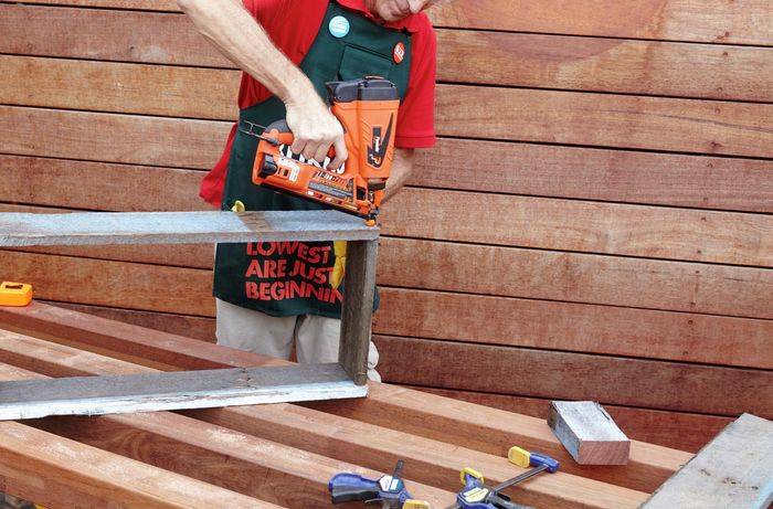 The frame of a herb planter being assembled by a Bunnings team member with a nail gun