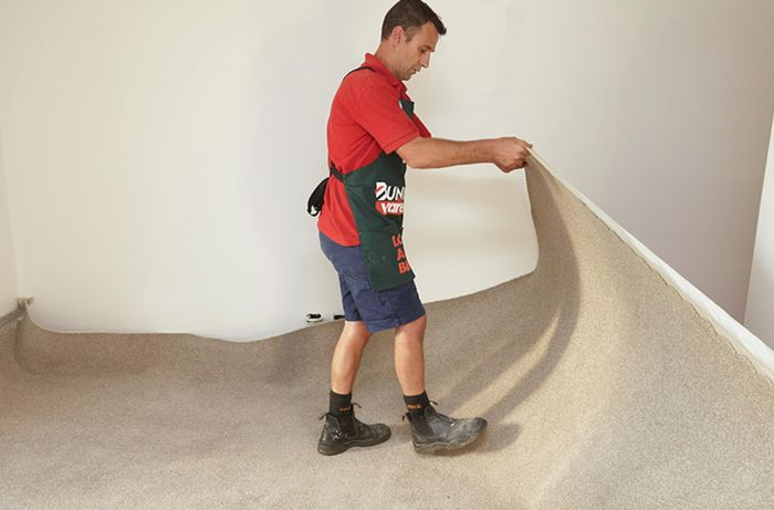 A Bunnings team member rolling out carpet into a cream-coloured room