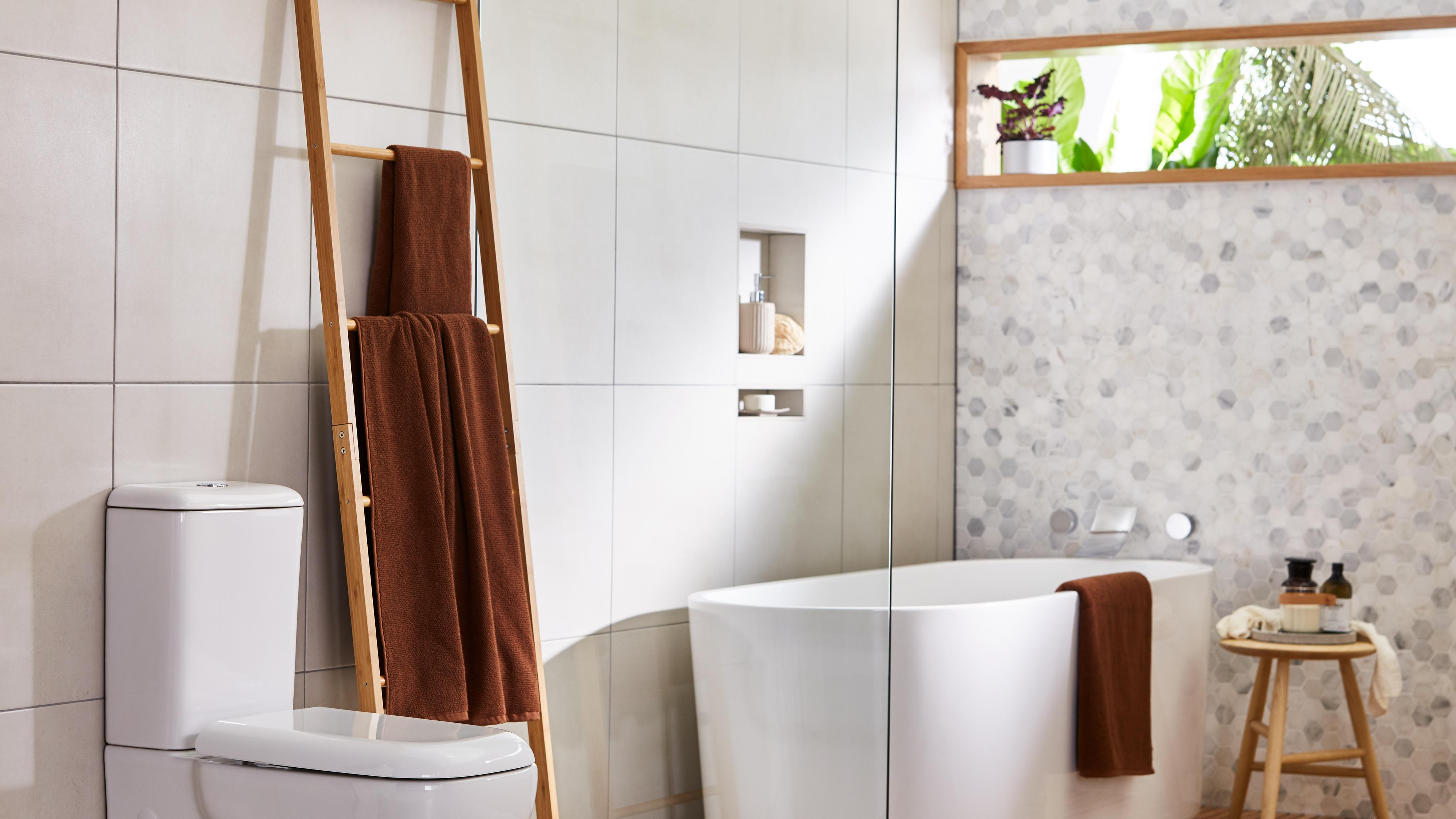Bathroom featuring large-tiled walls, bath, toilet and window with green plants outside.