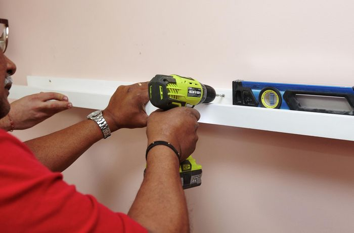 A person attaching a timber ledge to a wall using a cordless drill