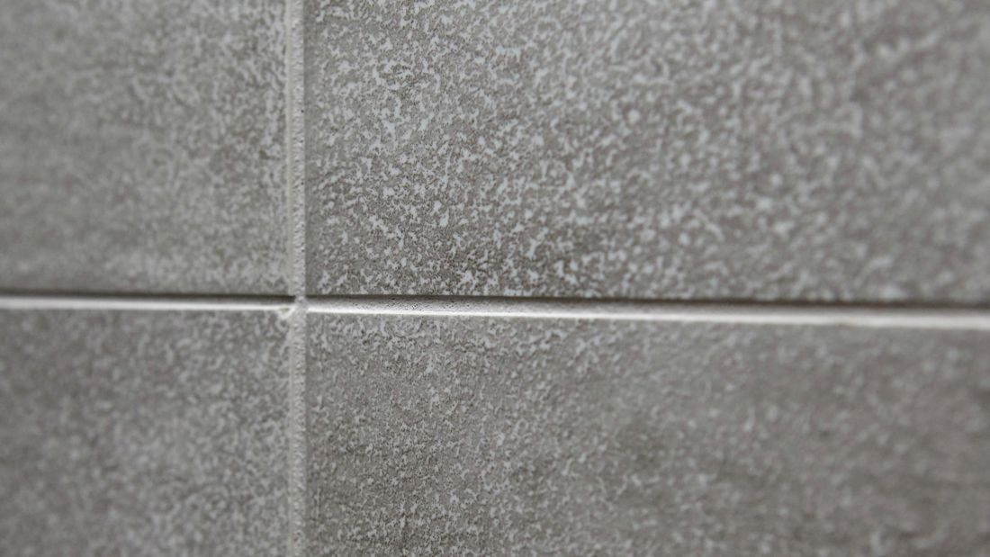 Closeup of grout between tiles on a wall