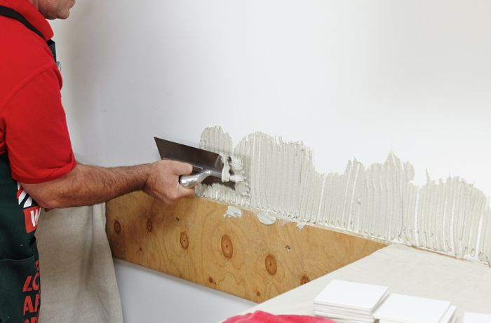 Person applying tile mastic to wall.